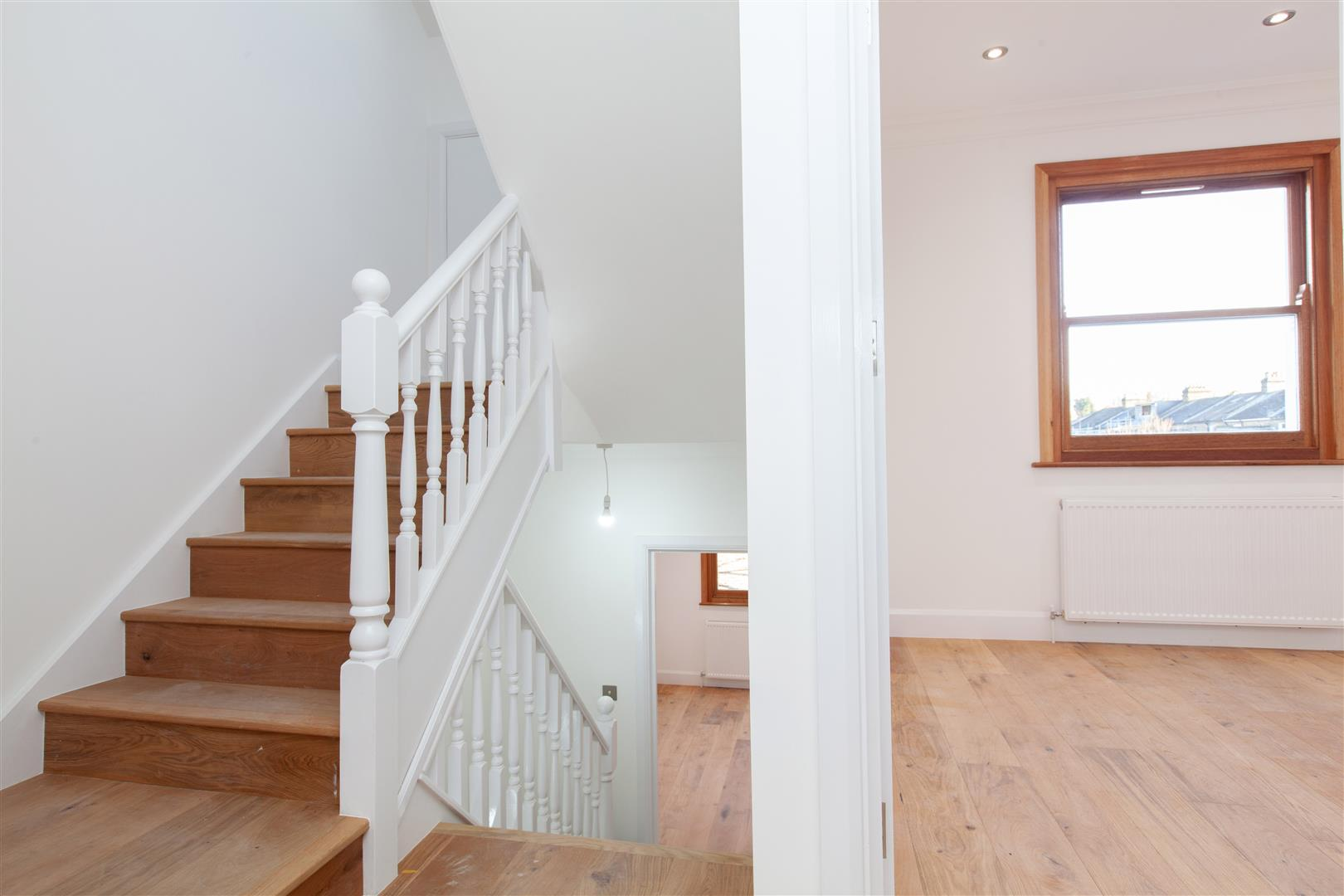 A picture of newly refurbished staircase with natural wood stairs leading to the lower ground level of Victorian townhouse.