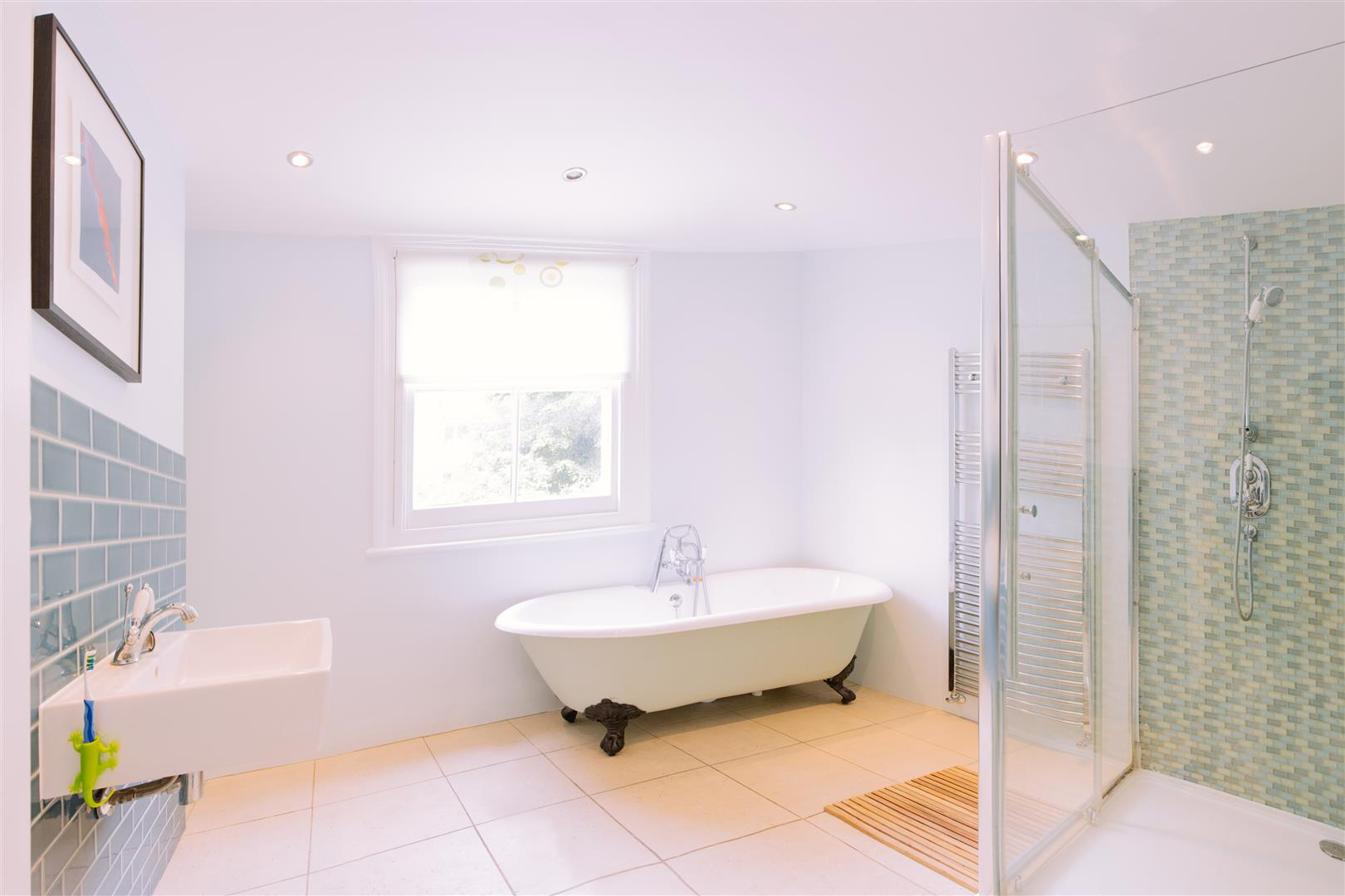 A picture of a large bright bathroom with a free standing bath, separate cubical shower and beautiful cream floor tiles.