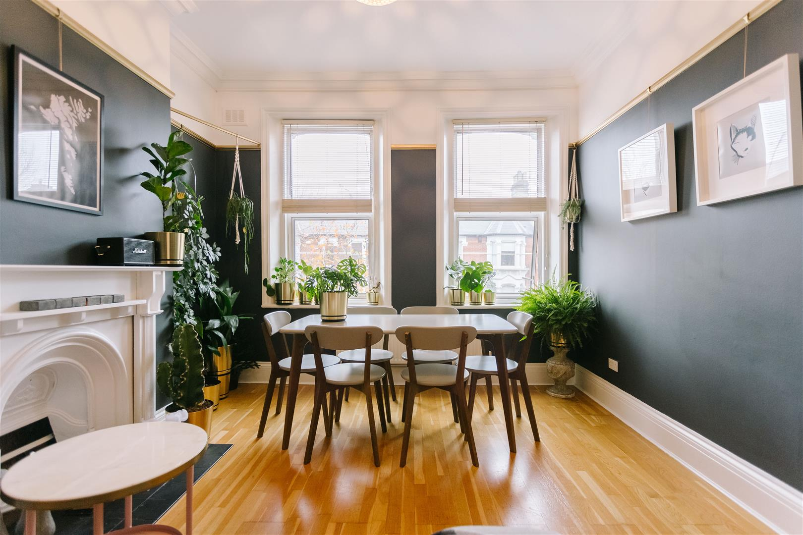 A Picture of a immaculate dinning room immaculately furnished, natural wooden floors and a selection of in door plants displayed to enhance the room.